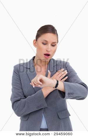 Shocked businesswoman looking at her watch against a white background