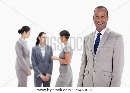 Close-up of a businessman smiling with three female co-workers talking seriously in the background