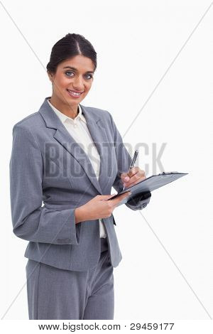Smiling female entrepreneur with clipboard and pen against a white background