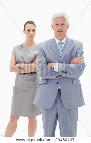 Serious white hair businessman with a woman behind him crossing their arms against white background