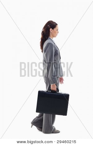 Profile of a businesswoman walking with a briefcase against white background