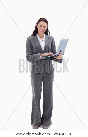 Businesswoman smiling with a laptop against white background