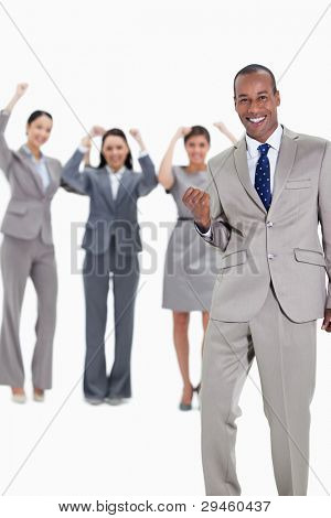 Successful business team with a happy businessman in foreground and three enthusiastic co-workers raising their arms