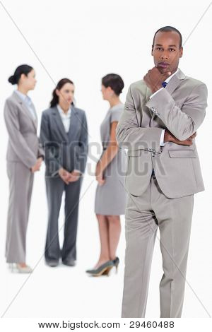 Serious businessman with a hand on his chin and three female co-workers talking seriously in the background