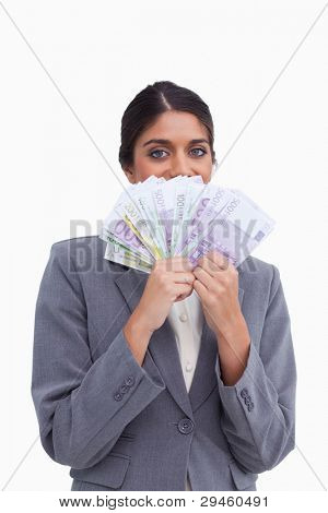 Female entrepreneur hiding her face behind bank notes against a white background