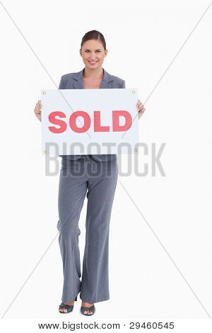 Happy real estate agent holding sold sign against a white background