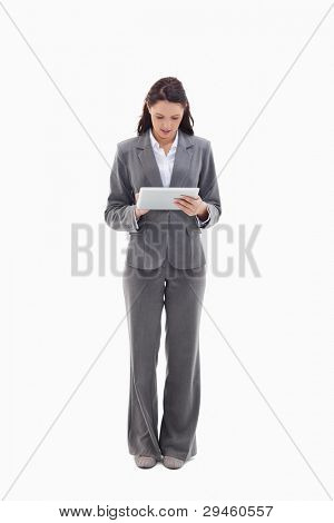 Businesswoman writing on a touch pad against white background