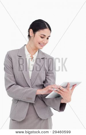 Smiling saleswoman using her tablet computer against a white background