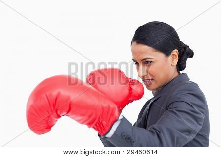 Close up side view of aggressive saleswoman with boxing gloves against a white background
