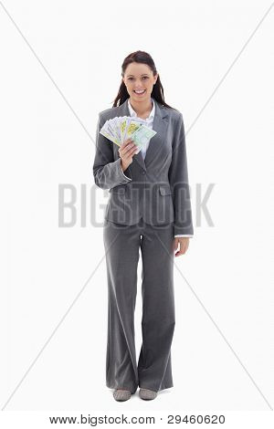 Businesswoman smiling with a lot of bank notes in her hand against white background