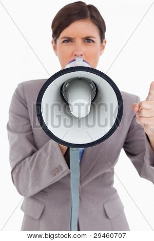 Close up of angry female entrepreneur shouting through megaphone against a white background