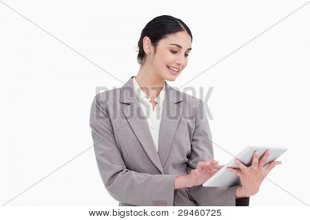 Smiling young businesswoman using tablet computer against a white background