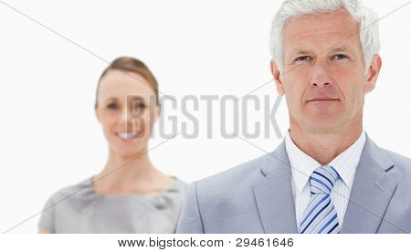 Close-up of a serious white hair businessman with a woman smiling behind him against white background