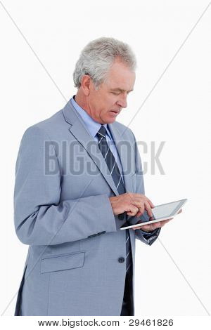 Side view of mature tradesman using tablet computer against a white background