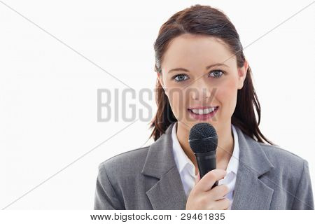 Close-up of a businesswoman holding a microphone against white background