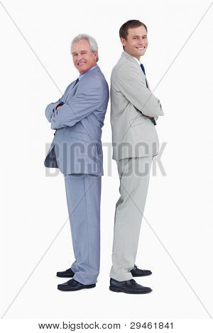 Smiling tradesmen standing back to back against a white background
