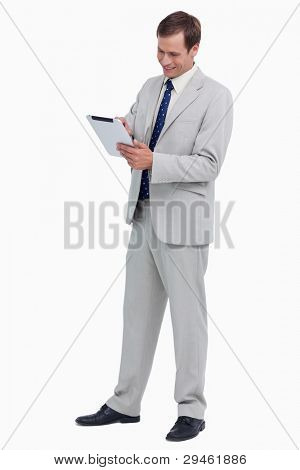 Smiling businessman using tablet computer against a white background