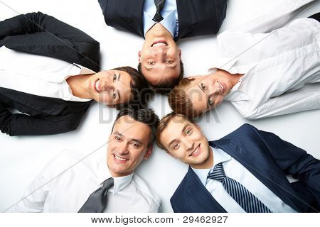 Five business people lying on the floor, looking at camera and smiling