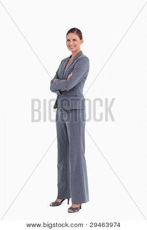 Side view of smiling tradeswoman with her arms folded against a white background