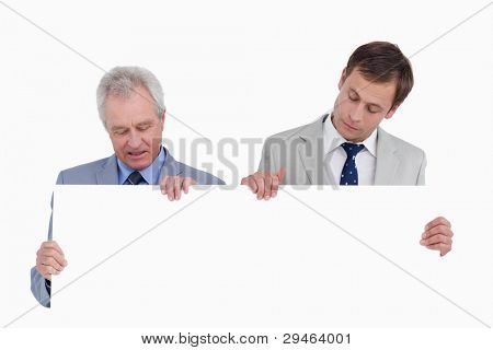 Tradesmen looking at blank sign in their hands against a white background