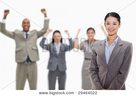 Close-up of a businesswoman smiling with enthusiastic co-workers raising their arms in the background
