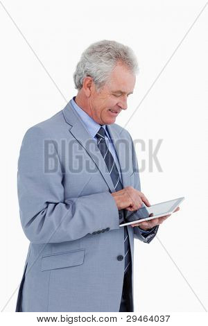 Side view of smiling mature tradesman using tablet computer against a white background