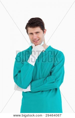 Close up of male doctor wearing scrubs in thinkers pose against a white background
