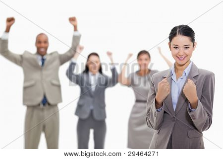 Close-up of a businesswoman smiling and clenching her fists with enthusiastic co-workers in the background