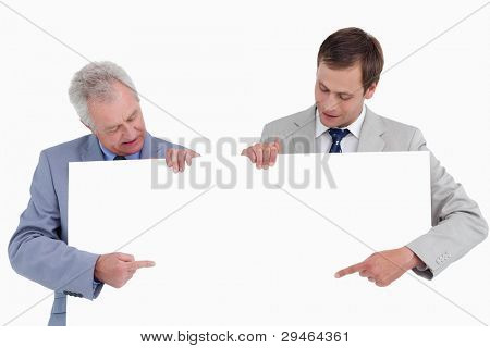 Tradesmen pointing at blank sign in their hands against a white background