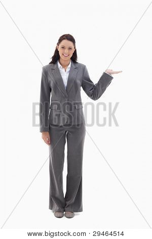 Smiling businesswoman and presenting a product against white background