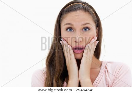 Close-up of a surprised young woman against white background