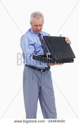 Mature tradesman taking a look into his suitcase against a white background