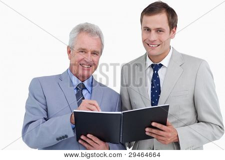 Smiling tradesmen taking notes in order book against a white background