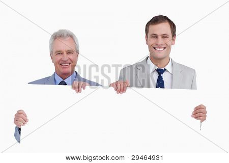 Smiling tradesmen holding blank sign against a white background