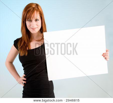 Pelirroja joven mujer con un cartel blanco en blanco