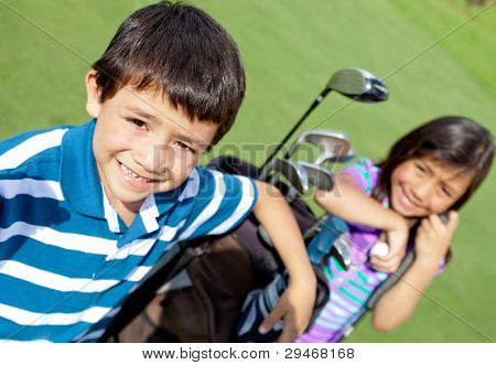Kids playing golf and holding a bag at the course