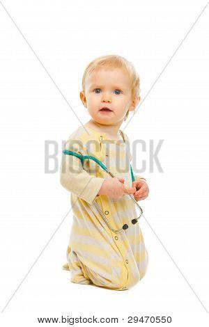 Bebé confundido con estetoscopio sentados en suelo aislado en Pentecostés