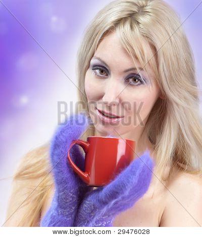 Retrato de la joven rubia en guantes suaves y con una taza