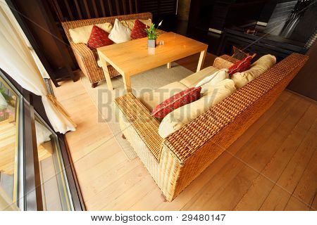 Two wicker couches with pillows and table in empty comfortable restaurant at day
