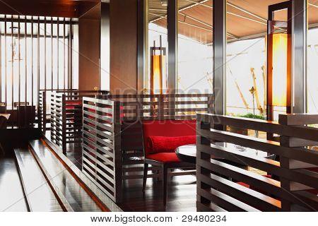 Zeile von Braun Tischen und rot sitzen in leere gemütliches Restaurant am Tag