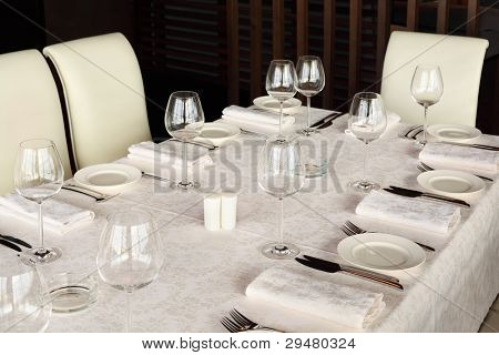 beautiful serving at table with white tablecloth in empty restaurant; glasses and plates