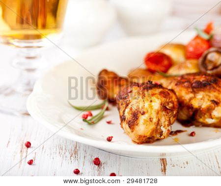 Roasted chicken legs with baked vegetables and a glass of beer in background