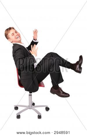Young Man In Suit Laugh Sits On Chair