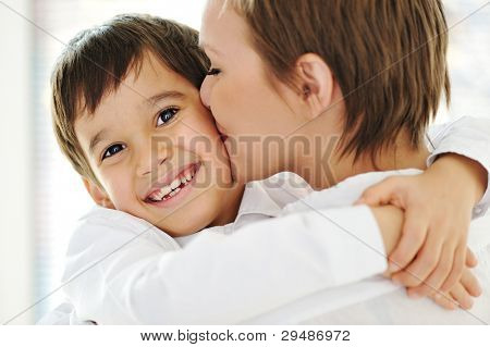 Happy mother embracing and kissing her son
