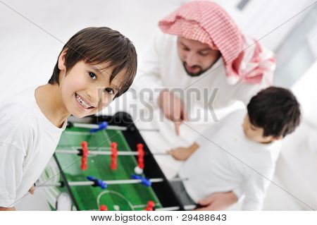 Arabic muslim family playing at home together, father and kids