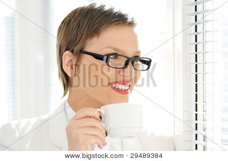 Young happy business woman drinking coffee while looking outside through window