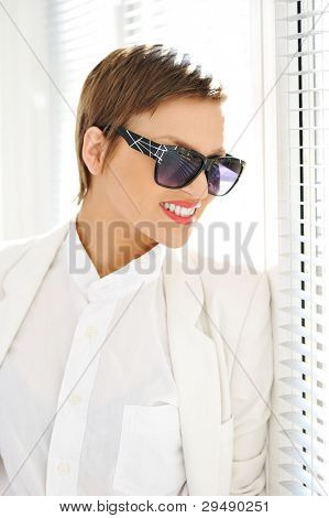 Fashionable business woman with sunglasses at window