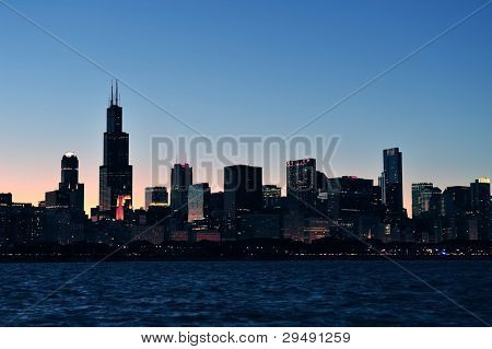 Chicago city urban skyline panorama silhouette at dusk with skyscrapers over Lake Michigan with clear sky.