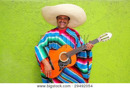 Mexican typical man playing guitar with poncho on green wall