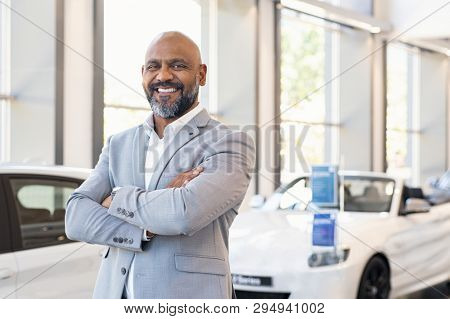 poster of Smiling businessman standing with arms crossed at new car showroom. Confident senior car dealer in d